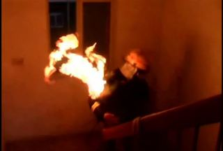 Firefighter carries burning gas tank to safety
